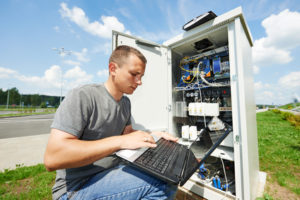 engineer working with laptop outdoors adjusting communication equipment in distribution box